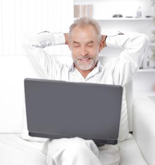 Senior geschäftsmann arbeitet am laptop in seinem büro.