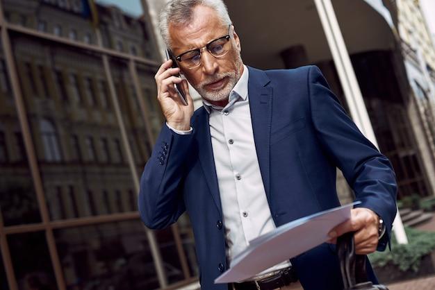 Senior geschäftsmann bespricht am telefon einen vertrag im freien in der nähe des büros