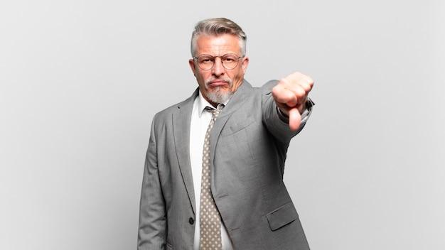 Senior geschäftsmann fühlt sich verärgert, wütend, verärgert, enttäuscht oder unzufrieden und zeigt daumen nach unten mit einem ernsten blick