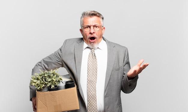 Senior geschäftsmann im ruhestand, der sich extrem schockiert und überrascht, ängstlich und panisch fühlt, mit einem gestressten und entsetzten blick