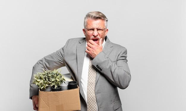 Senior geschäftsmann im ruhestand mit weit geöffnetem mund und augen und hand am kinn, unangenehm schockiert, sagt was oder wow