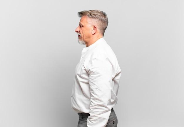 Senior geschäftsmann in der profilansicht, der den raum nach vorne kopieren möchte, denkt, sich vorstellt oder träumt