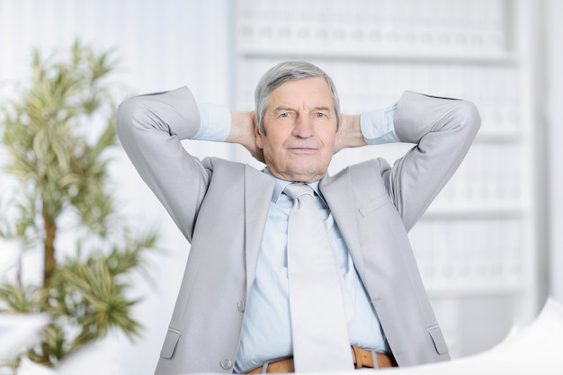 Senior geschäftsmann träumt davon, an seinem schreibtisch im büro zu sitzen