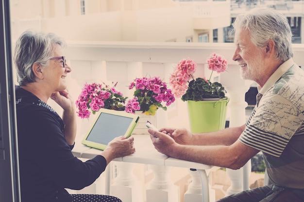 Senior glückliches kaukasisches paar in outdoor-freizeitaktivitäten mit technologie, chat-arbeit und videokonferenzen mit freunden. lifestyle zu hause in der heutigen zeit. konzept für moderne menschen im ruhestand