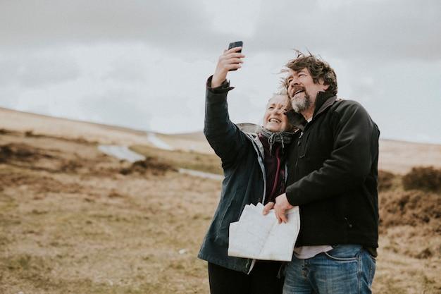 Senior glückliches paar unter selfies in wales, uk