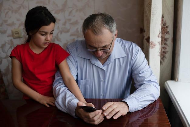Senior großvater mit kind mädchen enkelin zeit zusammen zu hause verbringen, im wohnzimmer sitzend, mit digitalem handy. videos ansehen, spiele spielen, soziale netzwerke