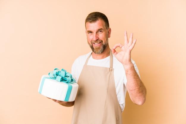 Senior hält einen kuchen auf beige wand fröhlich und zuversichtlich zeigt ok geste.