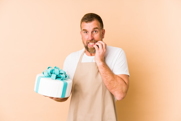 Senior hält einen kuchen isoliert auf beige beißenden fingernägeln, nervös und sehr ängstlich.