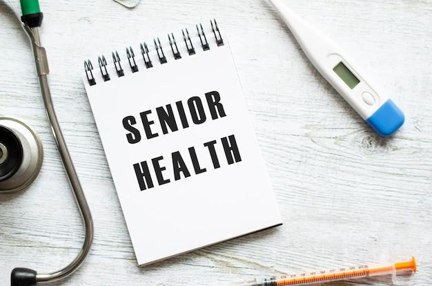 Senior health steht in einem notizbuch auf einem hellen holztisch neben einem stethoskop. medizinisches konzept