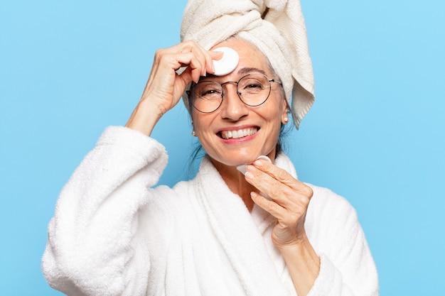 Senior hübsche frau gesichtsreinigung oder make-up nach der dusche mit bademantel