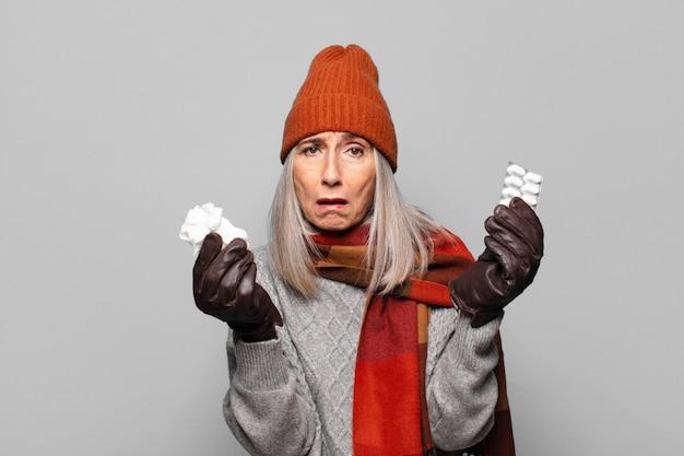 Senior hübsche frau mit einer pillentablette, die winterkleidung trägt. grippekonzept