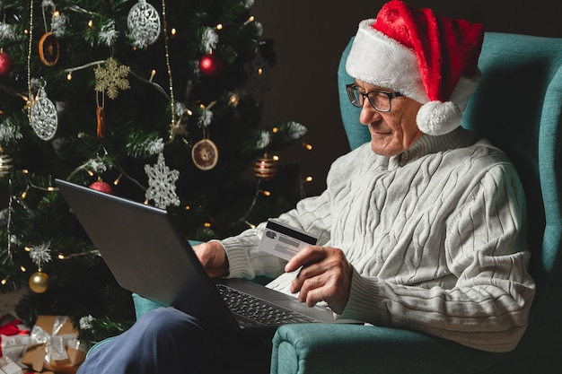 Senior in einer weihnachtsmannmütze sitzt in einem sessel unter verwendung des laptops, der kreditkarte auf dem entwurf eines weihnachtsbaumes hält