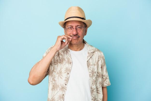 Senior indischen mann trägt sommerkleidung auf blauem hintergrund isoliert senior indische frau trägt ein afrikanisches kostüm isoliert auf weißem hintergrund mit den fingern auf den lippen hält ein geheimnis.