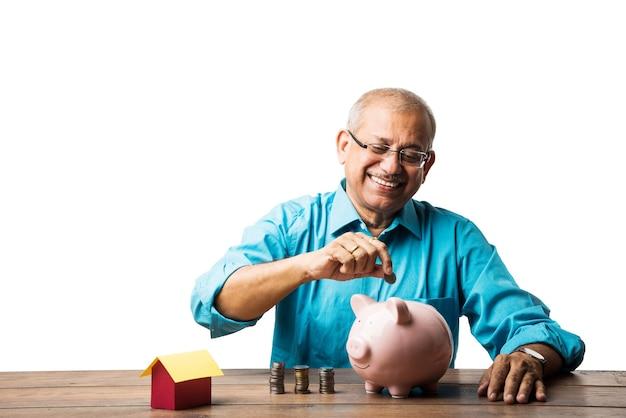 Senior indischer asiatischer mann und sparkonzept - mit sparschwein, banknoten, 3d-hausmodell, geldfächer, münzhaufen. am tisch sitzen