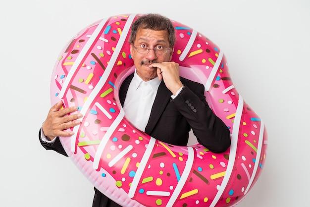 Senior indischer geschäftsmann hält aufblasbaren donut isoliert auf weißem hintergrund beißende fingernägel, nervös und sehr ängstlich.
