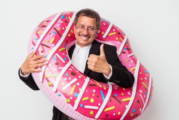 Senior indischer geschäftsmann hält aufblasbaren donut isoliert auf weißem hintergrund lächelnd und daumen hoch