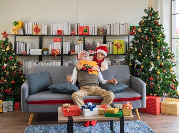 Senior kaukasischer mann aufgeregt mit überraschungsgeschenk von seiner frau hinter sich zu umarmen, während er auf der sofacouch im mit geschenken und weihnachtsbaum dekorierten wohnzimmer sitzt. romantik urlaub paar entspannen.