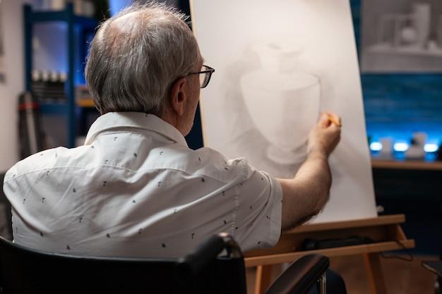 Senior-künstler mit handicap, der vasenzeichnung auf leinwand erstellt