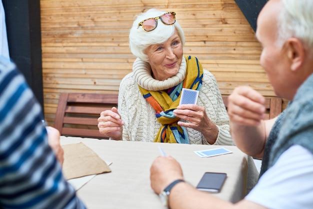 Senior lady spielkarten mit freunden