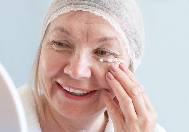Senior-lächeln der frau mit anti-aging-lotion. natürliche wellnessanwendungen, körperpflegekonzept, bio-kosmetik. anti-aging-konzept, gesundheitswesen und kosmetologie, ältere menschen, neue senioren