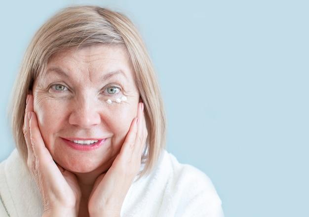 Senior-lächeln der frau mit anti-aging-lotion. natürliche wellnessanwendungen, körperpflegekonzept, bio-kosmetik. anti-aging-konzept, gesundheitswesen und kosmetologie, rentner und ältere menschen, neuer senior