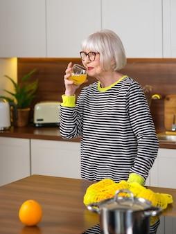 Senior lächelnde frau im gestreiften pullover hält orange und trinkt orangensaft in der küche