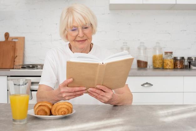 Senior liest ein buch in der küche