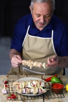 Senior männlicher koch bereitet kebabs zu. rohe hühnchen-spieße in den händen des kochs. grillvorbereitung.