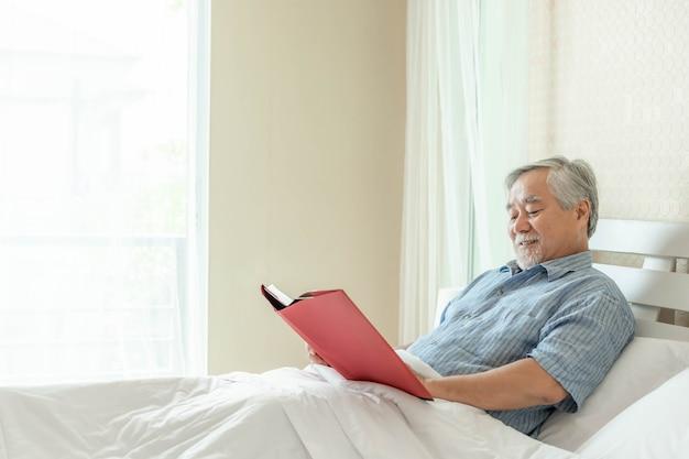 Senior male reading roman book, lächeln fühlen sich glücklich auf dem bett zu hause - lifestyle senior glück konzept