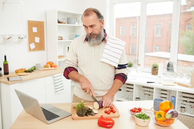 Senior man cooking von online tutorial