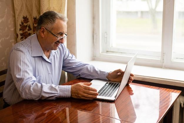 Senior man videokonferenzen auf laptop über schreibtisch aus holz