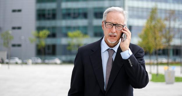 Senior manager am telefon zu fuß im freien