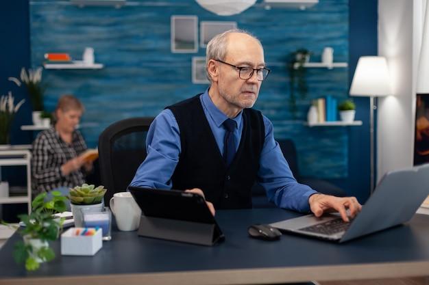 Senior manager, der an einer präsentation mit laptop und tablet-pc im büro arbeitet