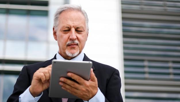 Senior manager, der eine digitale tablette im freien verwendet