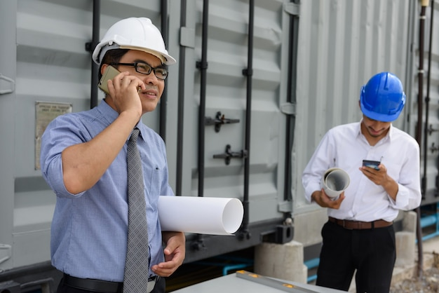 Senior manager des asiatischen ingenieurs hält blaupause und spricht auf der baustelle telefonisch, während junger ingenieur den projektplan liest.