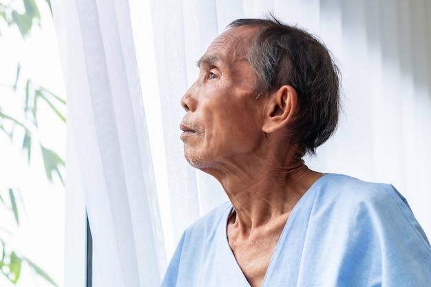 Senior mann geduldig denken und vom leben auf krankenhausbett träumen.