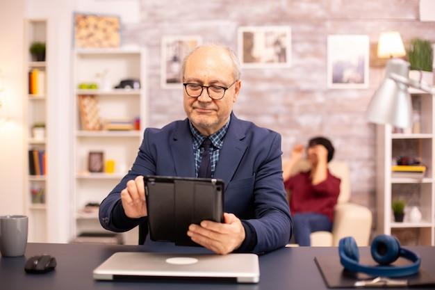 Senior mann in seinen 60ern mit einem modernen digitalen tablet in seinem gemütlichen zuhause