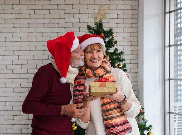 Senior mann küsst die wange seiner frau mit weihnachtsgeschenk in der hand zu hause im wohnzimmer. romantisches paar mit weihnachtsmütze feiern weihnachten zusammen mit glück.