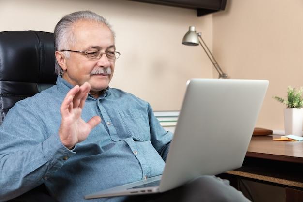 Senior mann online-kommunikation. alter mann macht videoanruf, der mit verwandten oder freunden per videokonferenz-app spricht