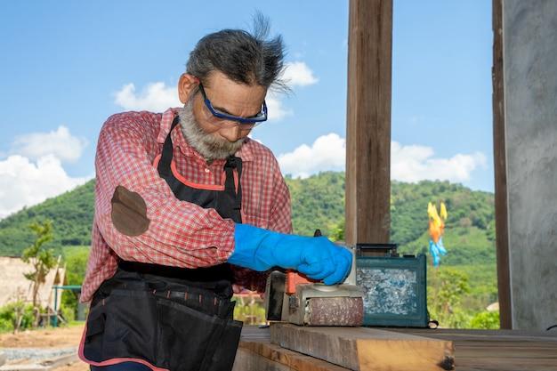 Senior mann zimmermann bei der arbeit mit jointer plane