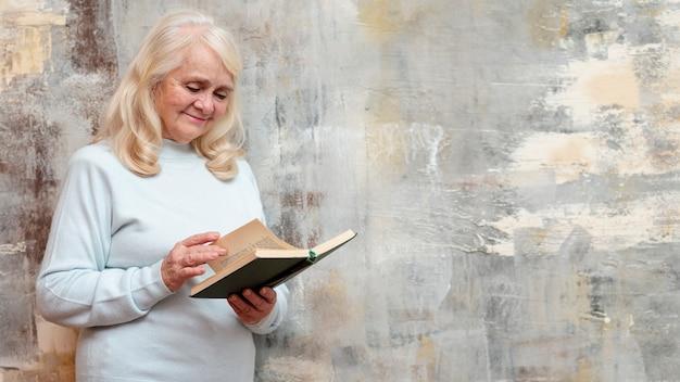 Senior mit der tagesordnung, die nahe bei gefrorenem fenster steht