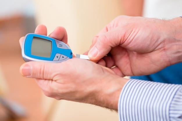 Senior mit diabetes mit blutzuckermessgerät
