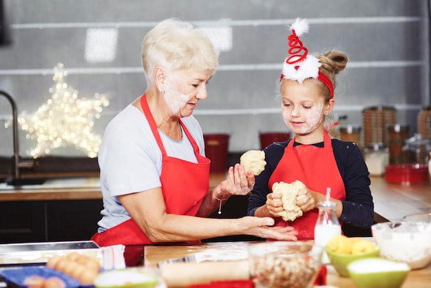 Senior mit mädchen, das teig in der küche knetet