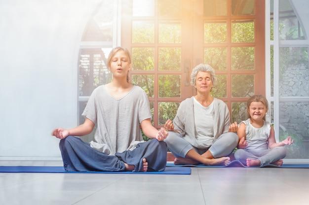 Senior mit teenager und enkeln, die zu hause yoga machen