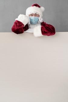 Senior mit weihnachtsmannkostüm und schutzmaske. mann, der leeres leeres brett hält. weihnachtsferien während des pandemie-coronavirus-covid-19-konzepts