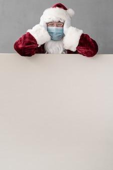 Senior mit weihnachtsmannkostüm und schutzmaske. mann, der leeres leeres brett hält. weihnachtsferien während des pandemie-coronavirus-covid-19-konzepts Premium Fotos