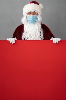 Senior mit weihnachtsmannkostüm und schutzmaske. mann, der rotes leeres leeres brett hält. weihnachtsferien während des pandemie-coronavirus-covid-19-konzepts Premium Fotos
