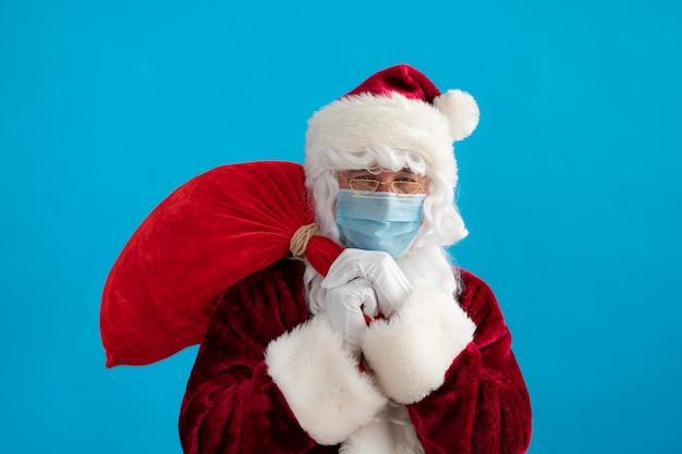 Senior mit weihnachtsmannkostüm und schutzmaske. mann, der tasche mit geschenken hält. weihnachtsferien während des pandemie-coronavirus-covid-19-konzepts