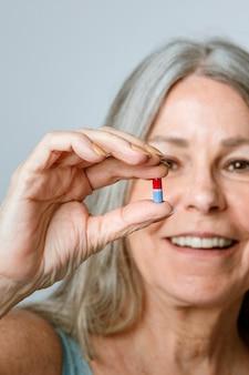 Senior nimmt eine pille gegen viruserkrankung ein