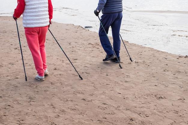 Senior nordic pole walker genießt schönen herbsttag im freien, in der nähe von meer. aktiver älterer mann und frau